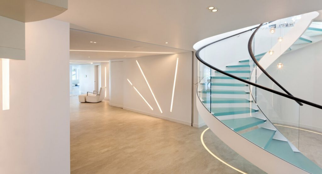 A modern basement and staircase lit with bespoke light fittings