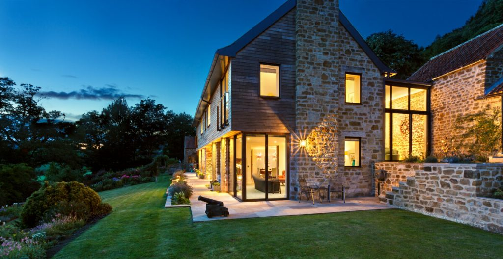 Subtle external lighting around a new build stone and timber new build house