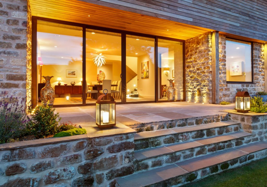 Ground recessed external uplights and carriage lights frame a stone terrace