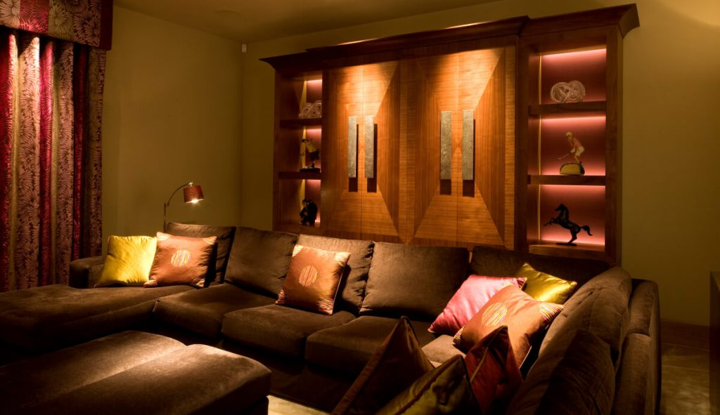 Lighting for shelving and richly covered sofa and cushions