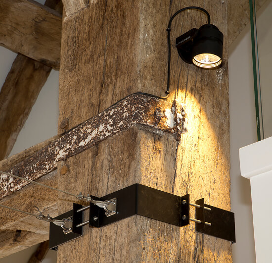 Detail of custom light fitting brackets on a beam in an old barn