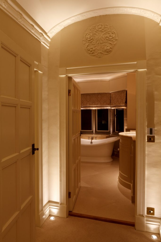 Arched doorway lit by powerful recessed LED uplights