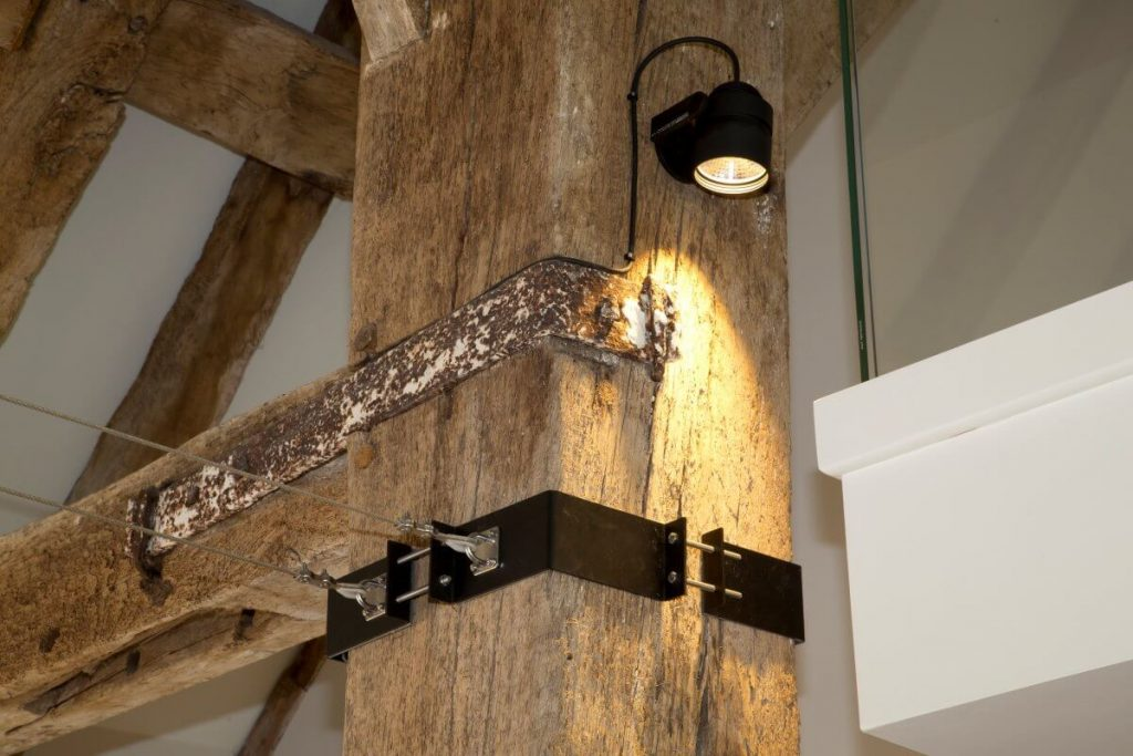Custom bracket clamping a beam in an old barn