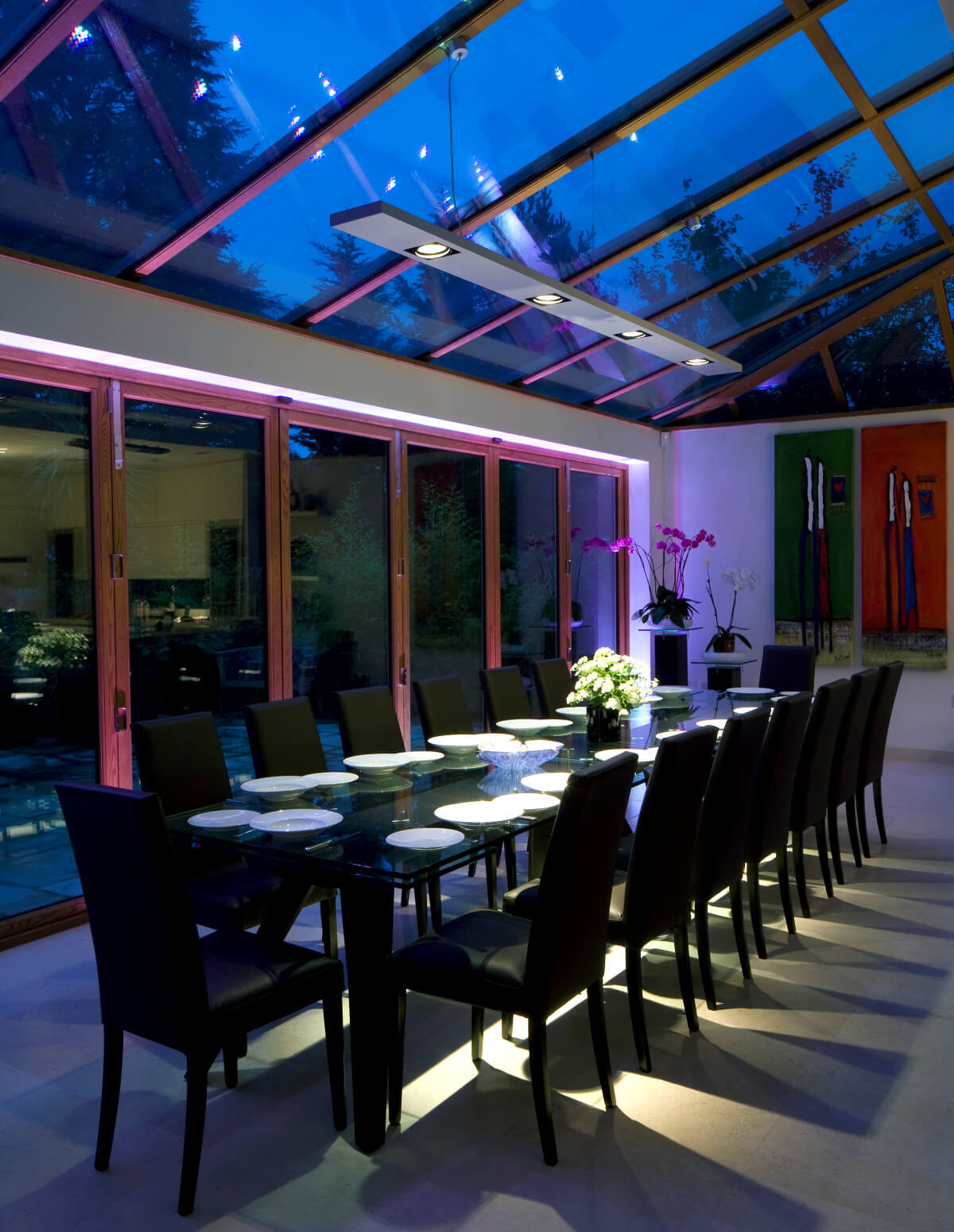 Dining table lit by suspended architectural profile with custom mounting points