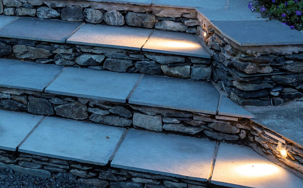 Step lighting detail. Small LED accent lights setting into stone walls shining across stone treads
