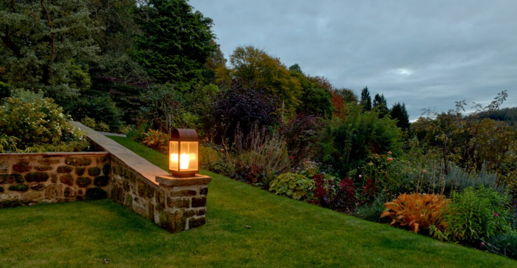 Garden lantern lighting a stone wall